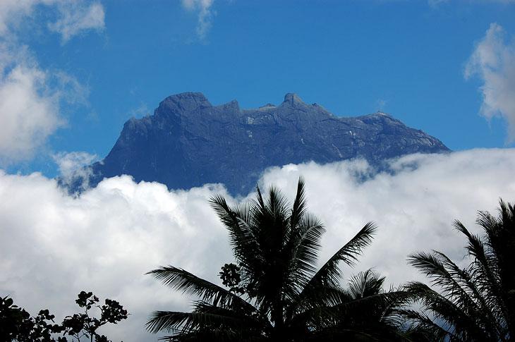 Это вершина Кинабалу, так сказать, на подступах. По склону спадает внушительного вида водопад, но конечно же густое покрытие из облаков мешает лицезреть эту струю воды. Впрочем, что на него смотреть, водопад как водопад. Гора как гора.