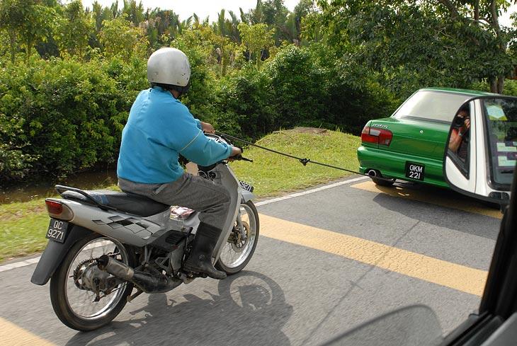 Это уже загородная трасса. Буксировка мотоциклиста.