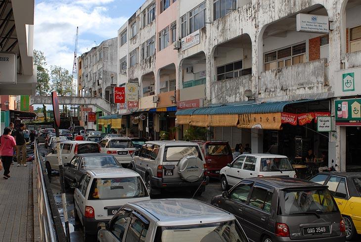 Толчея городских улиц. Прохожих мало, но машины иногда скапливаются в узких местах.
