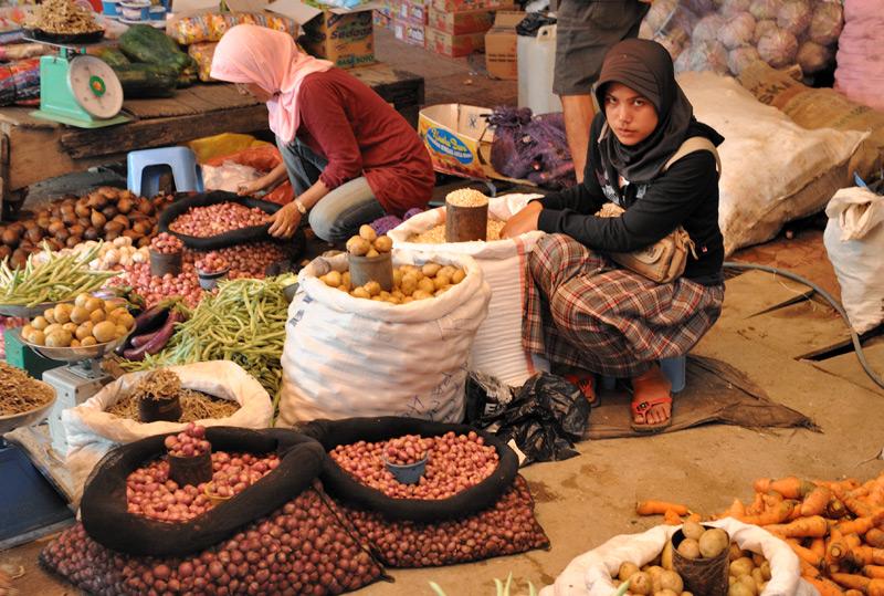 Милые мусульманские девушки торгуют чесноком и картошкой.