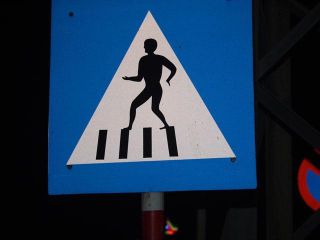 Очередной толстомясый дорожный знак. Изображает вороватого вьетнамца, что пиздит полосы разметки по мере перехождения дороги.