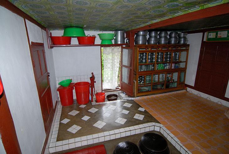 Демонстрирующий достаток и прочее благосостояние интерьер. Красная штуковина напоминает водяную колонку, но водопровода нет даже в многоэтажных домах. Воду таскают в ведрах. Высота дверных проемов примерно мне до плеча — не только в частных домах, но и в госучреждениях, например, в банке. В потолок тоже упираешься головой.