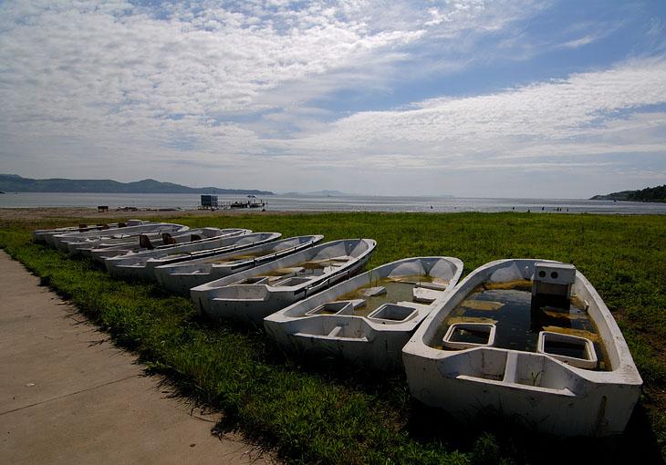 Лодки, вероятно, для катания туристов. Наполнены тухлой водой, источающей ужасающее зловоние на сотню метров. Пляж, в принципе, приличный, но вода достаточно холодная, и днем привозят толпы китайских туристов. В воду они не лезли, стояли одетые под зонтами на берегу, пялились на наши загорающие туши.