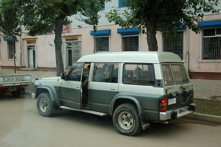Редкий цивильный кадр. Самый распространенный автомобиль — Ниссан Сафари. Такие ровные участки асфальта достаточная редкость, посему выбор транспортных средств понятен.