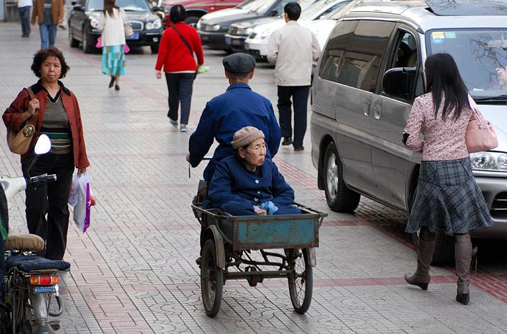 Не иначе любимую тещу везет. Вообще перевозка в кузове не очень характерна, видимо стариков принято всячески уважать и ублажать, а в старости в свою очередь принято садиться детям на шею. Типичная сцена, это транспортировка по               магазинам какой-нибудь наглой старушенции в национальной одежде. Ногами ей топать тяжко и лениво, а сидеть дома в углу не принято. Поэтому коляски, в которых молодежь катает своих предков, встречаются чуть ли не реже велосипедов.
