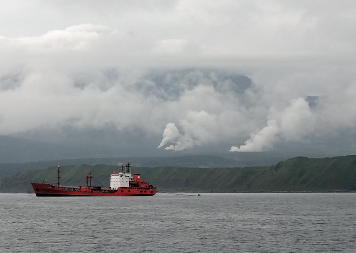 Наконец, обрулив утыканный огнями Хоккайдо, наш броненосец встал на рейд Южно-Курильска. В предтайфунном затишье, сквозь туман,               показался Кунашир, многочисленными дымами вулканического попердывания полностью оправдывая название островов - Курилы.