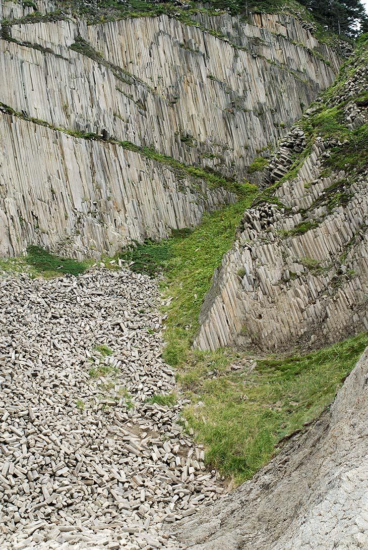 Скалы в виде огромных пучков аккуратных каменных граненых кристаллов. Безумные шестиугольники образуют неприступные утесы, преграждающие блуждающим пешеходам путь по пляжам из черного песка.