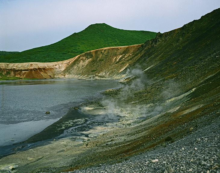 Из озера Кипящего вытекает ручей, впадающий в озеро Горячее. Под ногами, сквозь вулканический пепел, пробиваются струйки сернистого газа, что-то булькает и хрюкает, исторгая черные пузыри со дна водоема.