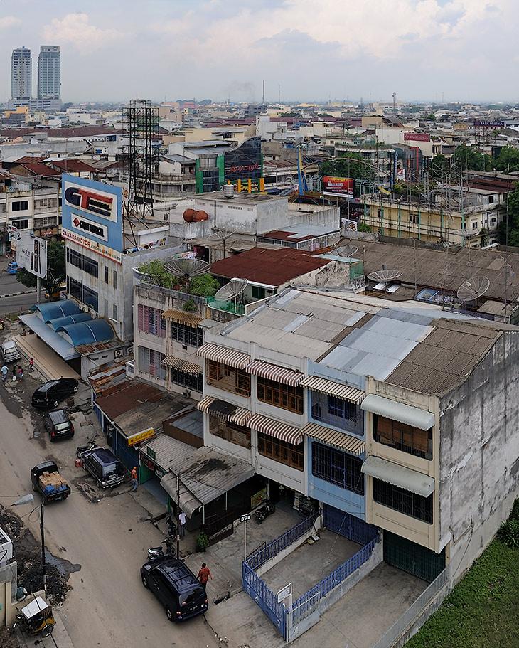 Высоких зданий мало, крыши традиционных азиатских муравейников ощетинились ажурными антеннами. Однообразную серость бетона               оживляют ржавые вывески, да охапки трепыхающегося на веревках белья.