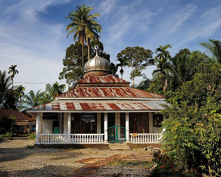 Типичная мечеть в одной из мелькающих вдоль нашего пути деревушек. Культовые сооружения слегка кособокие, подобно любому               местному зданию. Ржавые крыши, грунтовые дворики. Чаще всего, мечеть расположена у реки или иного водоема. Иногда, вплотную с ней,               построена католическая церковь. Особого религиозного рвения в суматранцах не наблюдается. Индонезия, официально - самое большое               мусульманское государство, при ближайшем рассмотрении оказывается многоконфессионально. И большинство населения не отягощено               религиозным фанатизмом.