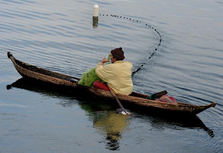 Уже привычные долбленые лодки, сети и важные мужики в вязаных шапках, словно клопы-водомерки скользят они по отражению зажатого мохнатыми утесами неба.