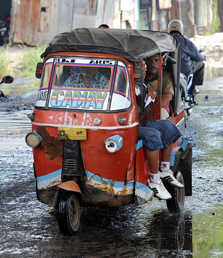 Словно трескучие красные жуки снуют по городу трехколесные, набитые избыточным количеством пассажиров, такси.