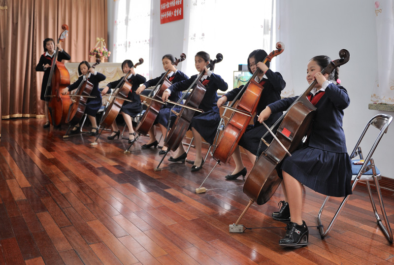 Пионеры наяривают на музыкальных инструментах с мастерством профессиональных оркестрантов.
