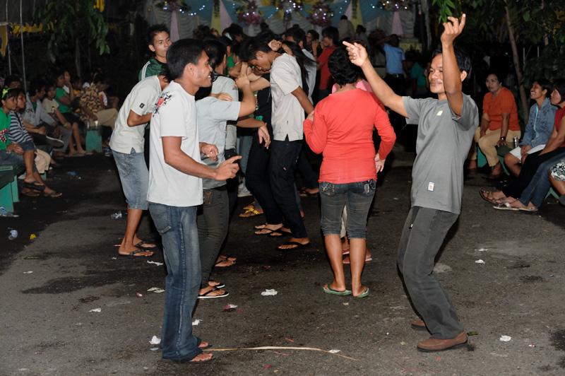 Под навесом в темноте истошно бубнит музыка, слегка трезвые гости извиваются в коллективном танце.