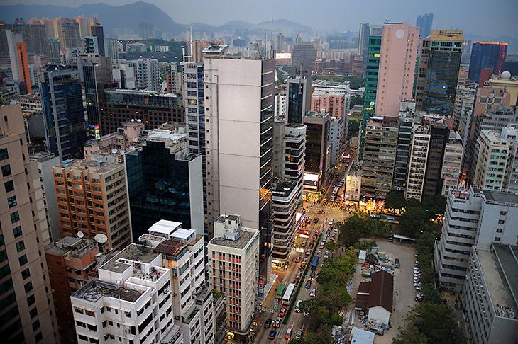 Сквозь грязное стекло нашего, находящегося на хрен знает каком этаже, пристанища открывается вечерний вид на материковую часть               Гонконга, не имеющую, впрочем, принципиальных отличий от части островной. Обратите внимание на крышу белого здания в левом нижнем углу               снимка.