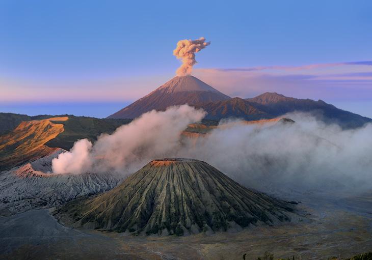 Внутри десятикилометрового разрушенного древнего кратера Танггер (Tengger), взорвавшегося еще несколько миллионов лет тому               назад, портят атмосферу несколько активных вулканов: Бромо (Bromo), Баток (Batok) и Курси (Kursi), с возвышающимся позади всего этого               безобразия вулканом Семеру (Semeru). Эти тектонические прыщи полагается наблюдать с вершины горы Пенаджакан (Penajakan), восхищаясь               вздымающимися в синее небо смрадными клубами вулканических газов. Толпы страждущих дыма и зрелищ зевак январскими воробьями жмутся на               холодном ветру, встречая лениво встающее над каменными морщинами кровавое солнце.