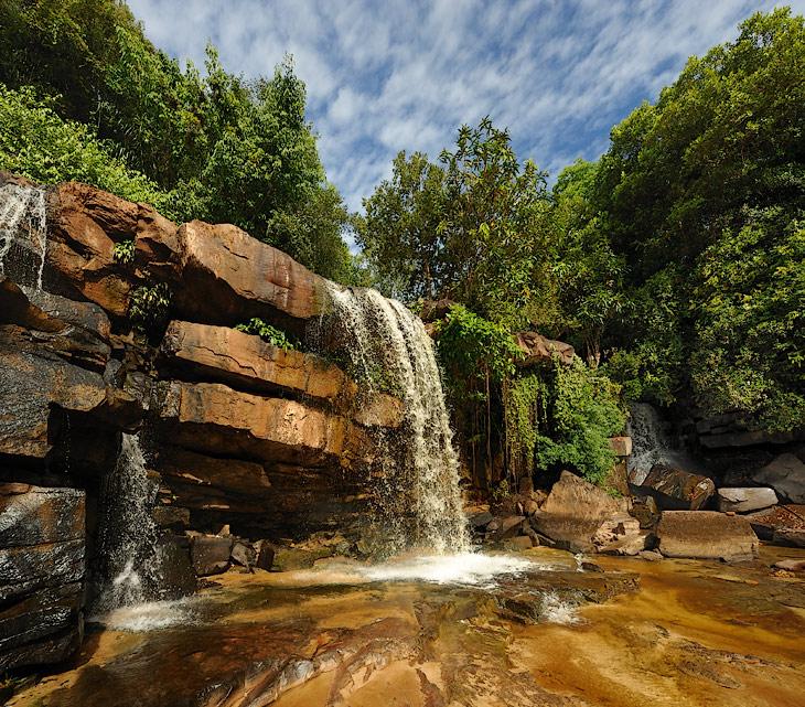 Водопад Кбаль Чхай (Kbal Chhay) - как и все пресноводные объекты Камбоджи сильно зависит от сезона. Сейчас, во время засухи, это исключительно красивый ручей, меж причудливого нагромождения скал, а не мутный поток бурлящей             жидкости. Утреннее солнце делает особенно сочными и без того крикливые цвета мокрых камней.